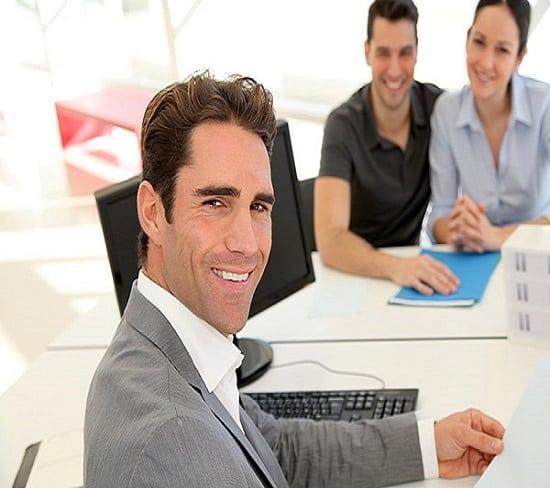 Agente di viaggio in giacca e cravatta e nello sfondo dei clienti